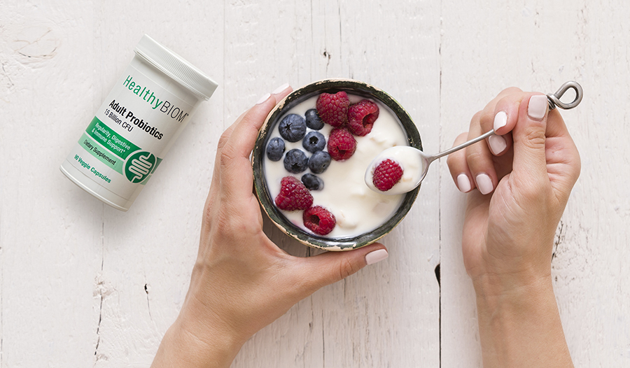 Healthy yogurt with berries in a bowl on a table with bottle of probiotics