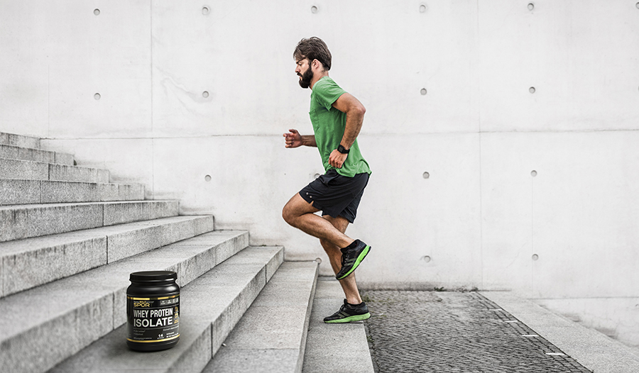 Male athlete running up stairs outside with bottle of whey protein