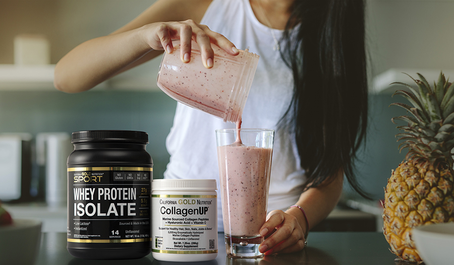 Woman making smoothie in kitchen with whey protein, collagen, and pineapple
