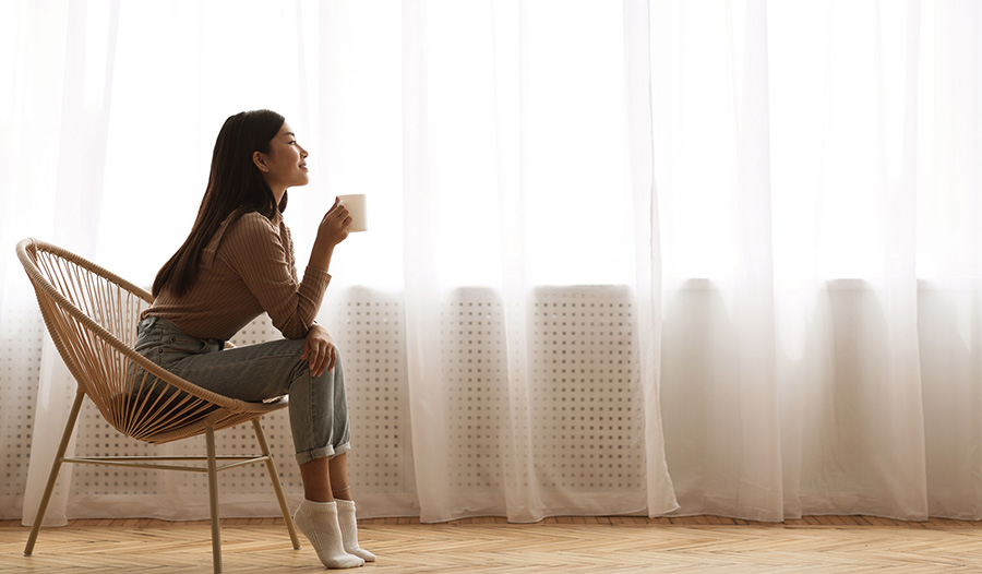 woman practicing self care by sipping coffee by the window