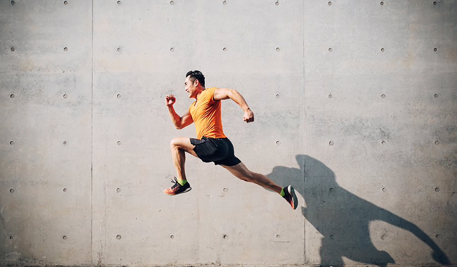 Fit healthy Asian man in orange shirt running
