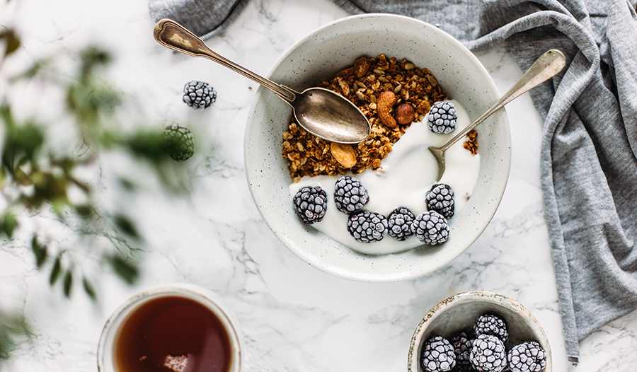 Yogurt with blackberries and granola on a marble table