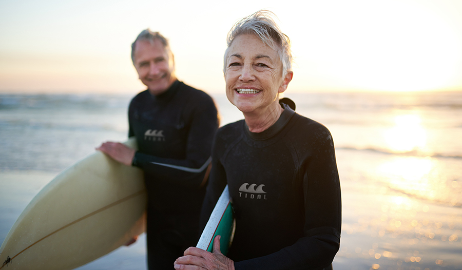 Mature woman and man smile on the beach with surfboards