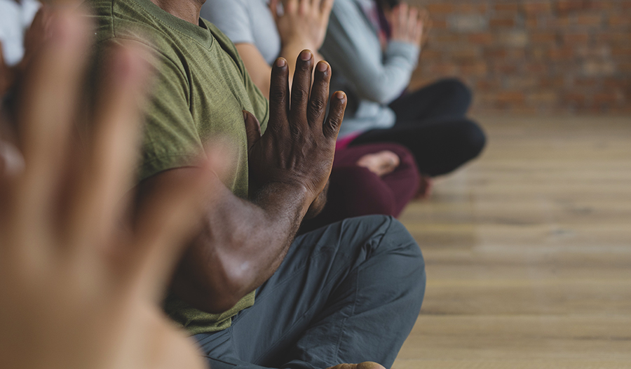 Man in green shirt in a group of people meditating with hands together in prayer