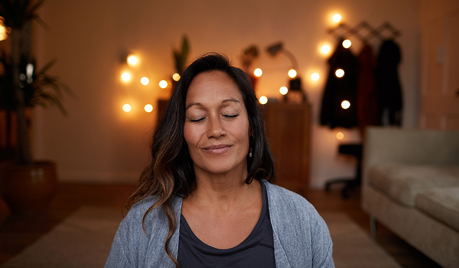 Meditating woman smiling with her eyes closed while sitting on her living room floor practicing yoga