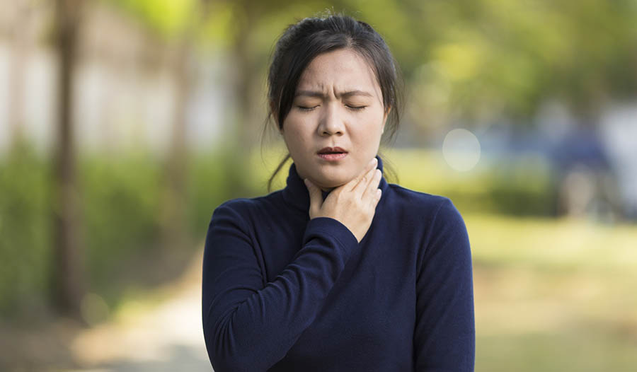 Asian woman holding throat experiencing acid reflux or heartburn