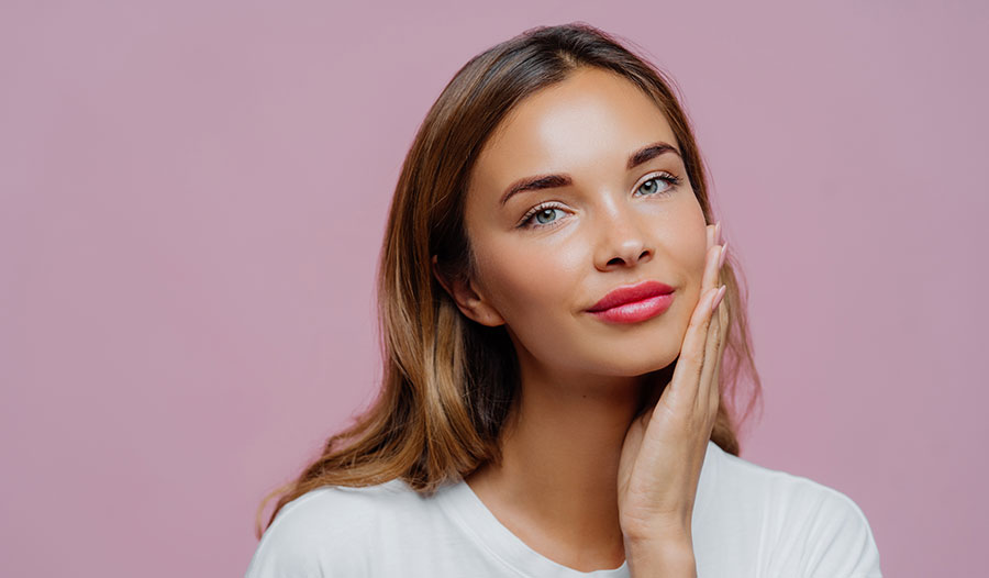 woman with glowing skin touching her face with one hand against a mauve background