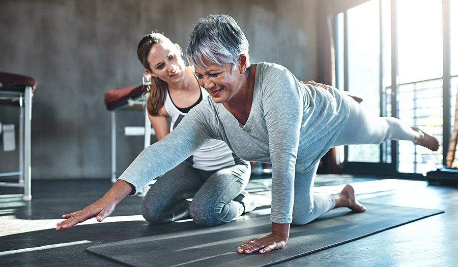 Female trainer working with client on yoga mat