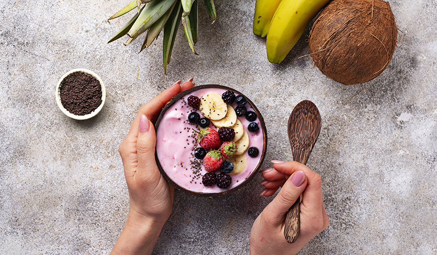 Acai smoothie bowl with fresh fruit toppings and chia seeds on concrete table