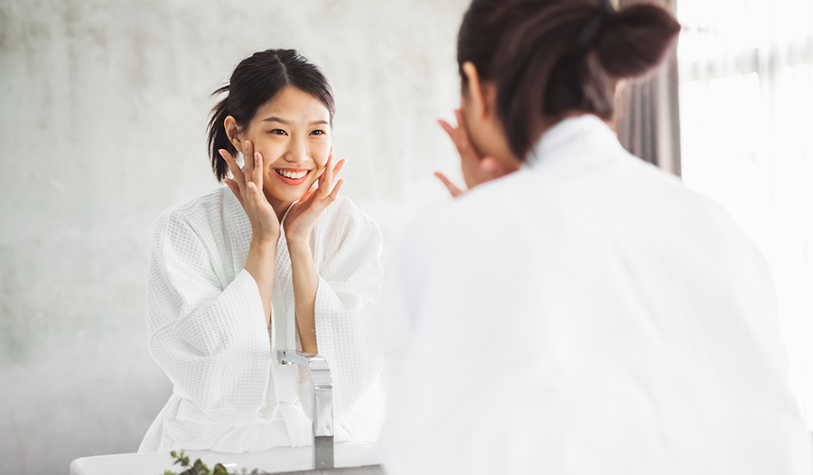 Asian woman washing face and applying skincare products in bathroom