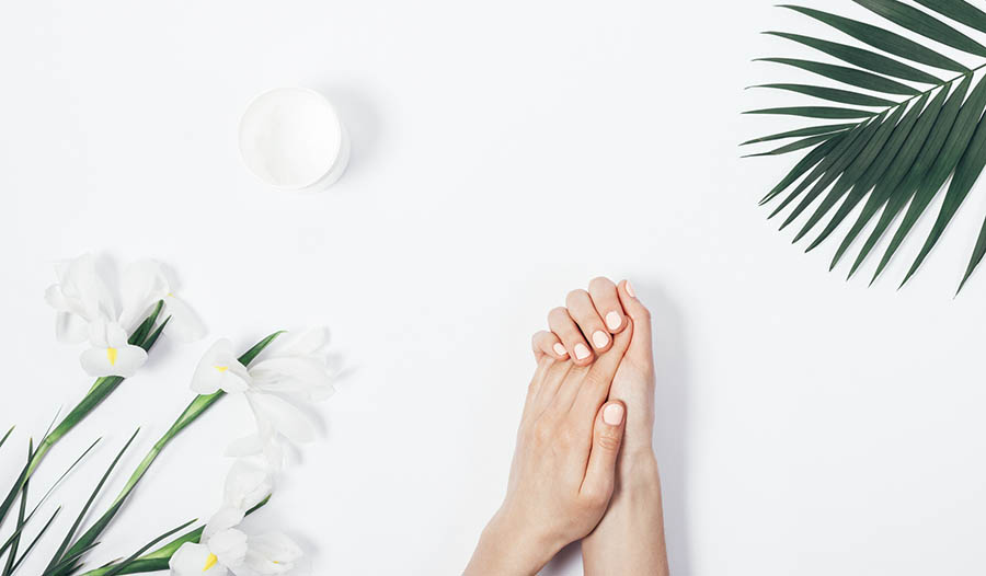 Hands and lotion on white background with tropical leaves