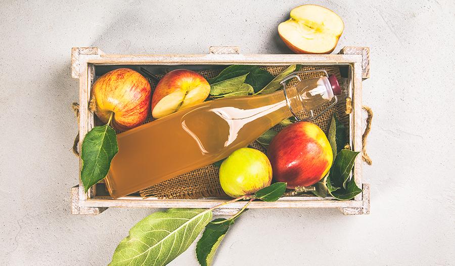 Apple cider vinegar and fresh apples in wooden box