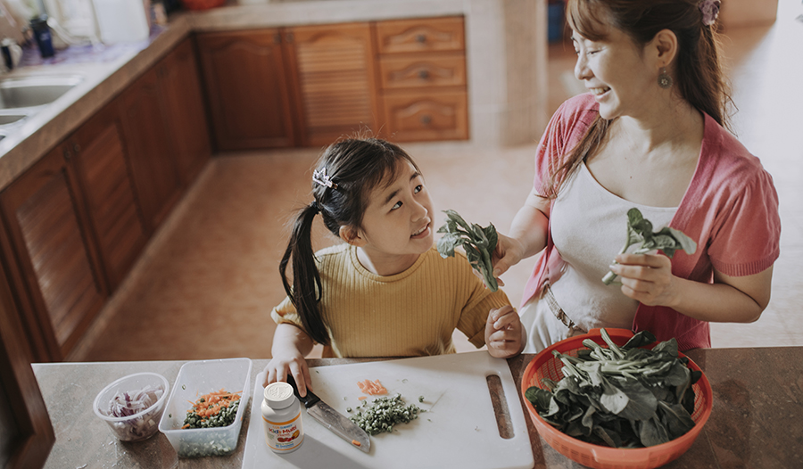 Asian mother and daughter cooking healthy meal in the kitchen