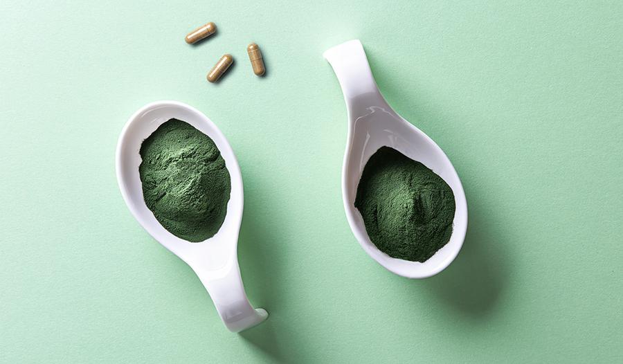 Bladderwrack supplements and spirulina powder on green background