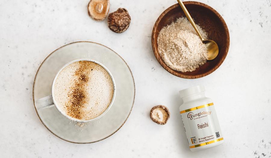 Mushroom supplement on table with coffee, mushrooms, and mushroom powder