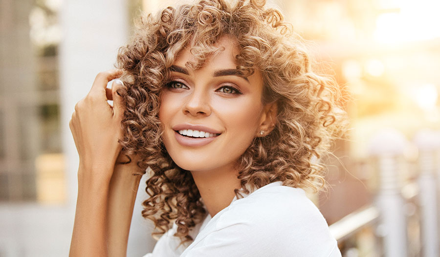 woman with curly hair thinking about the different types of hair masks she can use