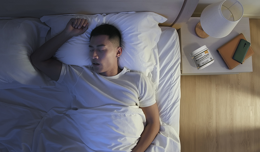 Man asleep at home with magnesium powder and phone on bedside table