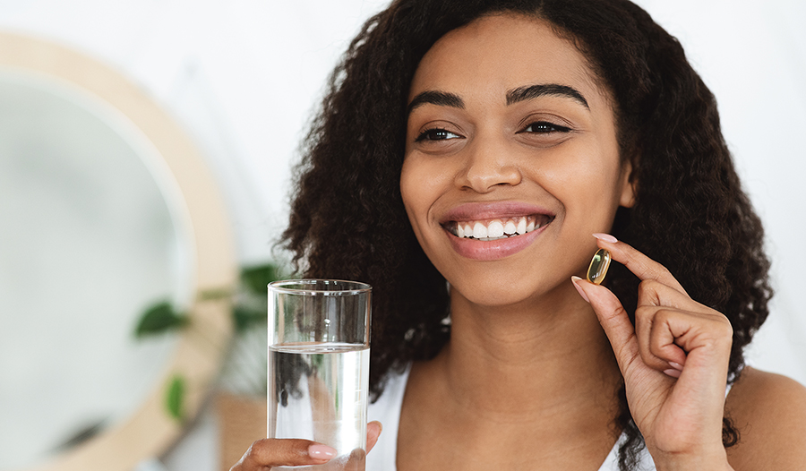 Woman with healthy skin and hair taking fish oil supplement with water