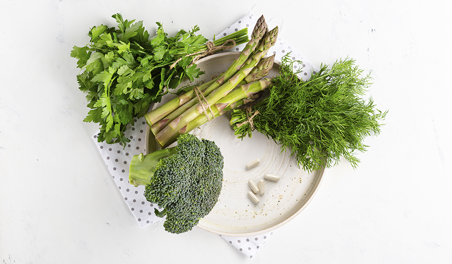 Green vegetables on plate with betaine HCL supplements