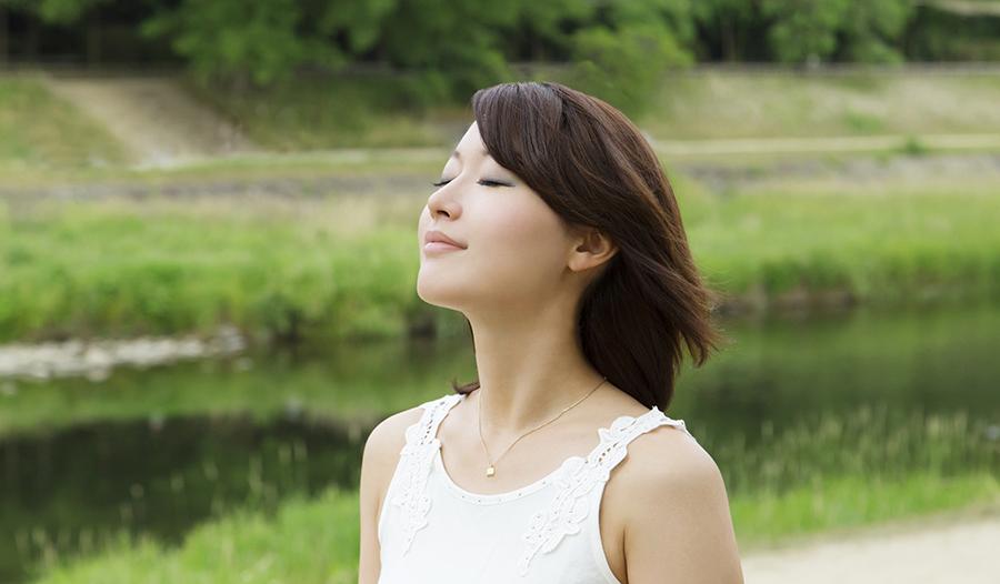 Asian woman taking deep breath outside