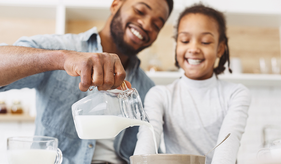 Young dad and daughter pouring milk into cereal for breakfast