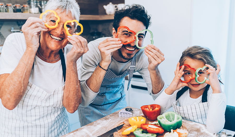Happy multi-generation family cutting peppers and cooking dinner in the kitchen
