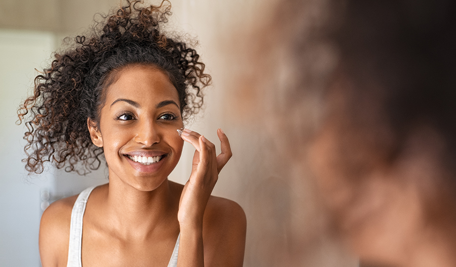 woman applying skincare products for her skin type to her face