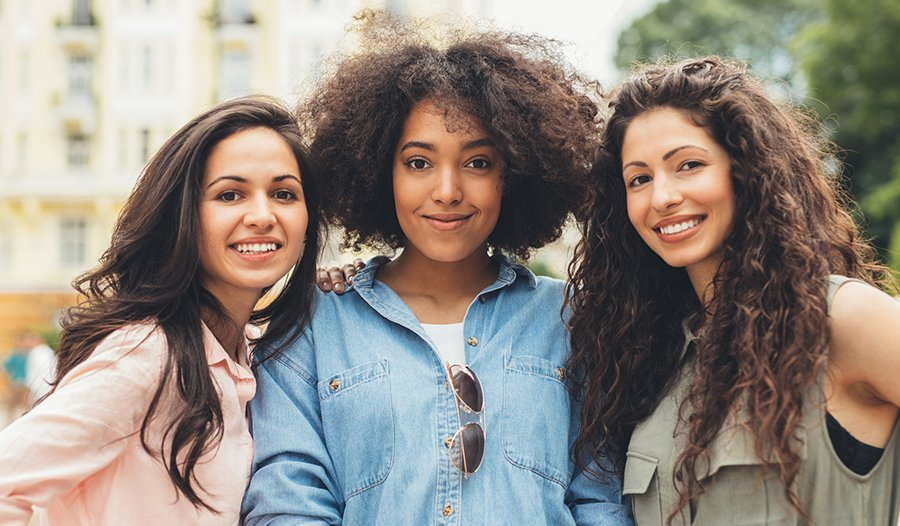 three women with different hair types standing together