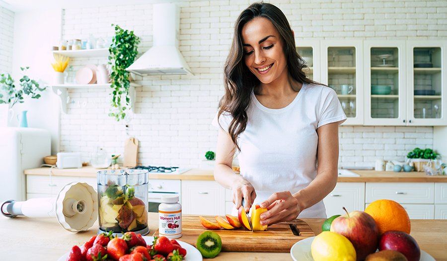 Young woman making a fruit smoothie in the kitchen