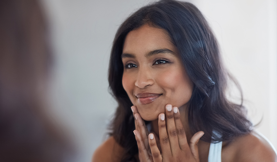 woman looking at her skin in mirror thinking of questions to ask her dermatologist