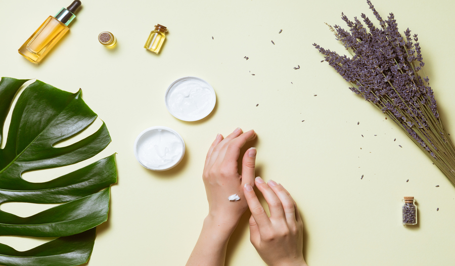dry hands with a dab of lotion against a yellow background and a palm leaf, oils and other moisturiz