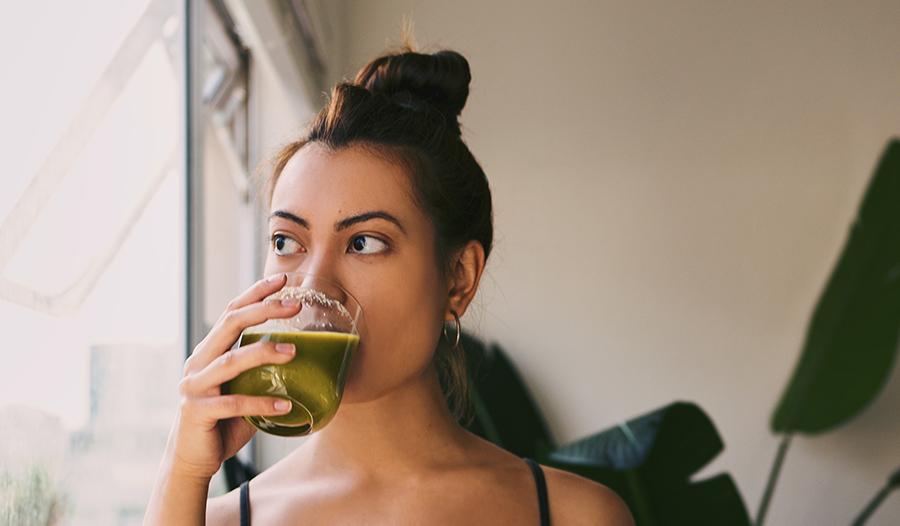 Healthy woman drinking green juice by the window