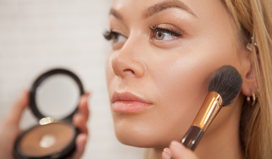 makeup artist applying double duty makeup products to model's face
