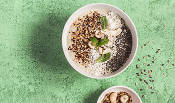 Healthy smoothie bowl with nuts and chia seeds on green table