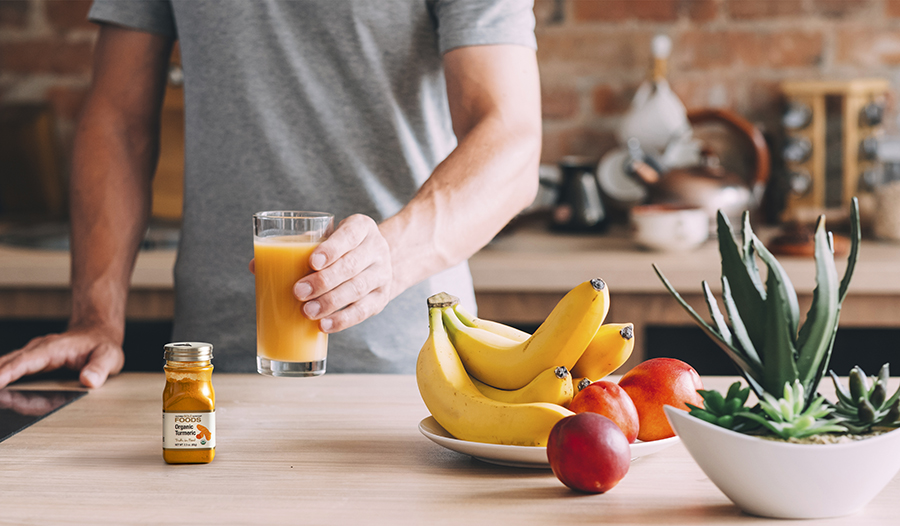 Man drinking fresh juice in kitchen with turmeric and fruits