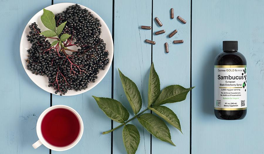 Elderberry fruit, leaves, and supplement bottle on blue table