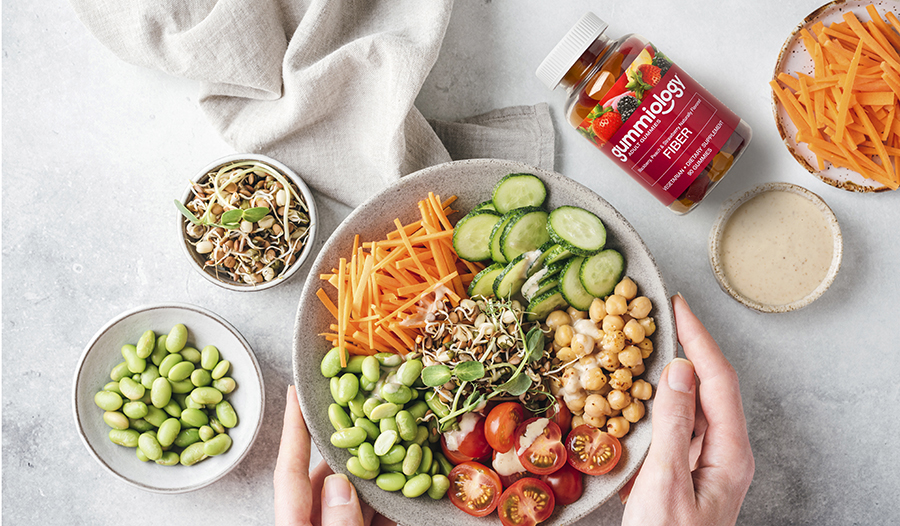 Fiber-rich salad bowl full of vegetables on table with fiber supplement