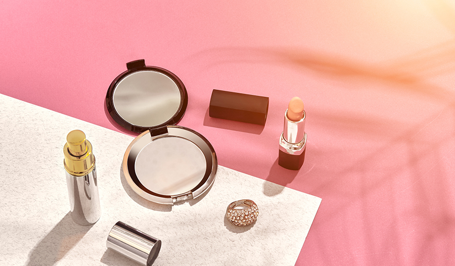 flat lay summer makeup against sunset gradient background