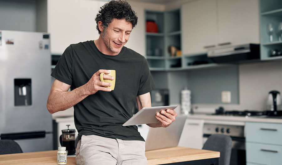Man drinking coffee in kitchen looking at tablet