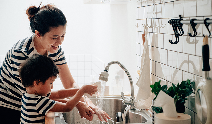 Asian boy washing dishes with his mother in the kitchen