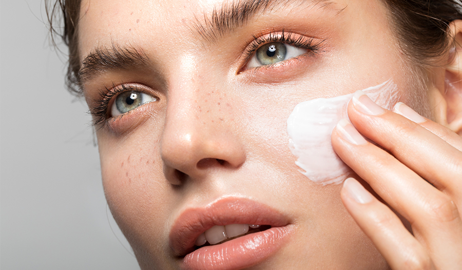 portrait of woman applying makeup primer to her face