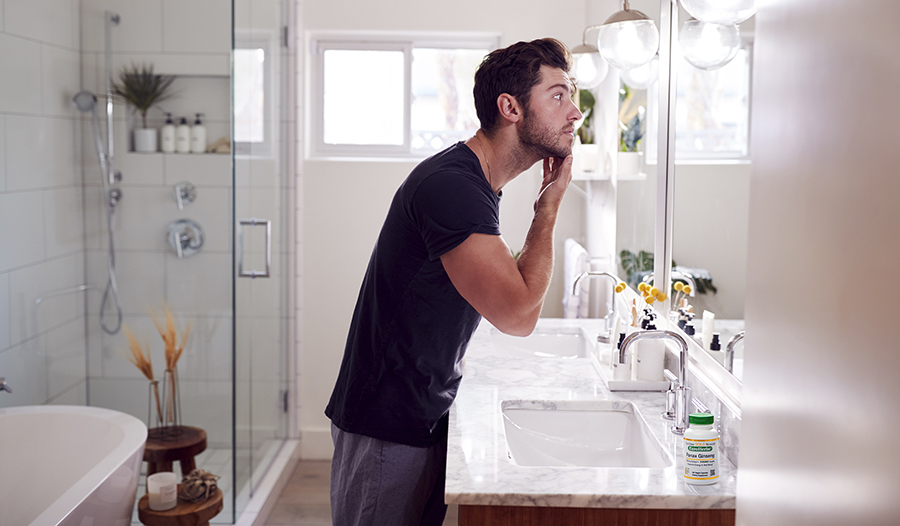 Man standing in bathroom looking in mirror