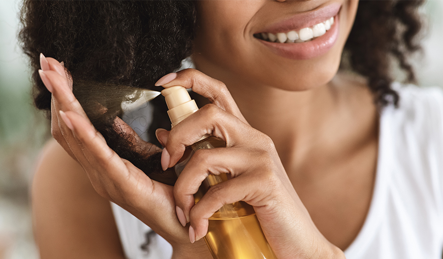 woman applying hair oil to her natural hair