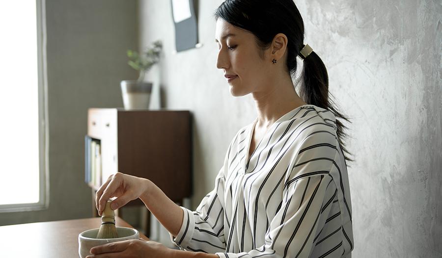 Young Asian woman making traditional matcha at home