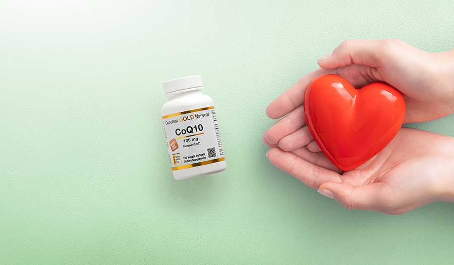 Hands holding red ceramic heart on green background with CoQ10 supplement