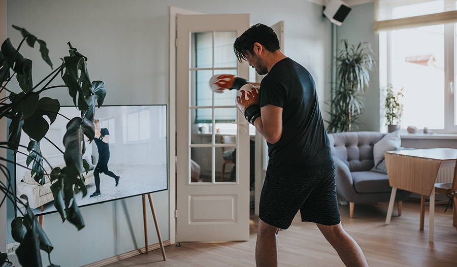 Asian man wearing boxing gloves does boxing workout video at home