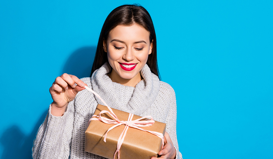 woman against blue background opening a wrapped gift