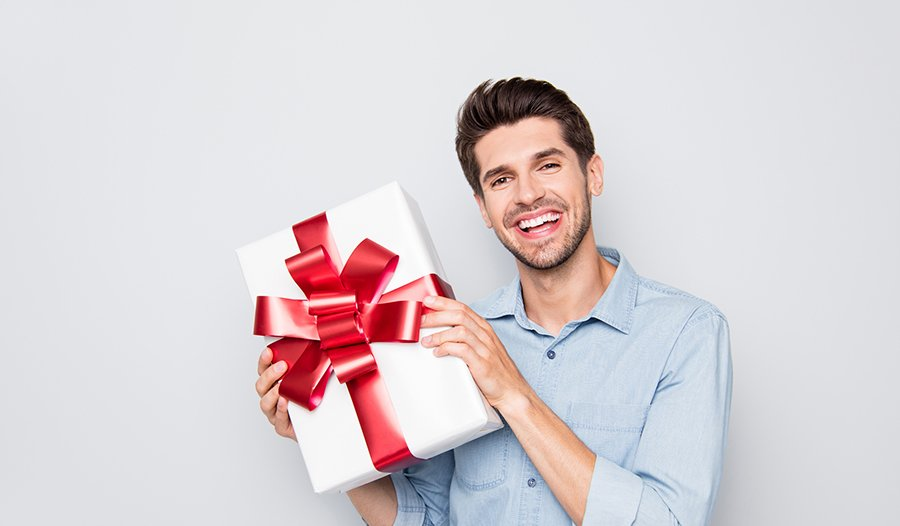 cheerful man holding up wrapped holiday gift