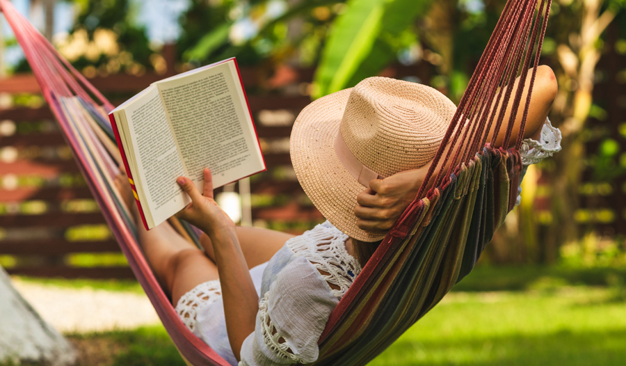 woman in hammock reading a book for self-care