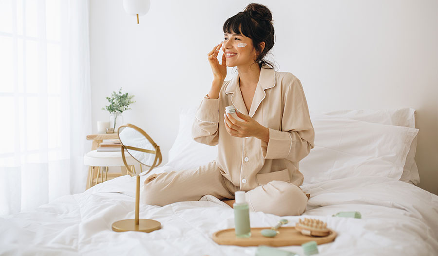 woman sitting on bed applying clean beauty products to her face